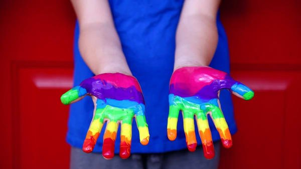Image shows someone with their hands painted using the human rights global colours